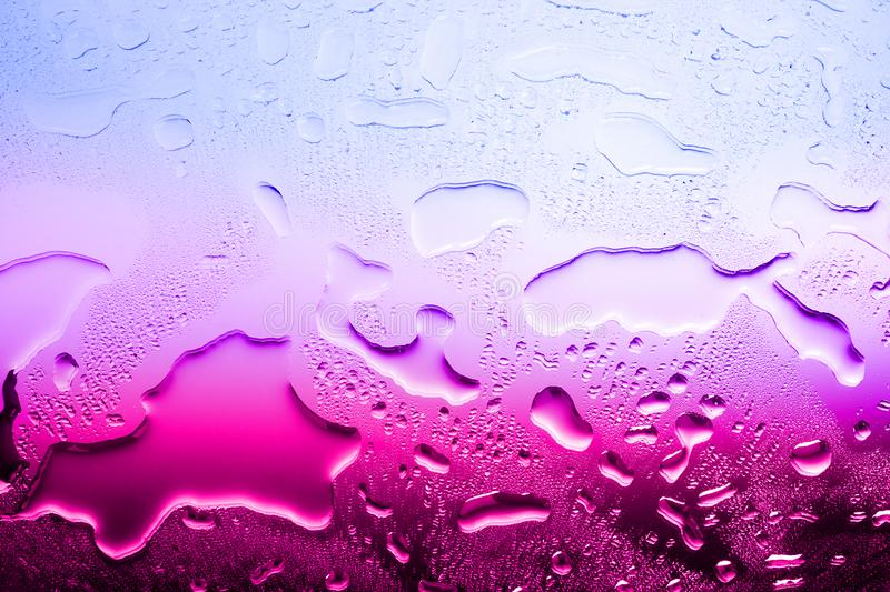Wet glass surface, water drops, gradient color from blue to red, illustration of world warming, texture of spilled water royalty free stock photography