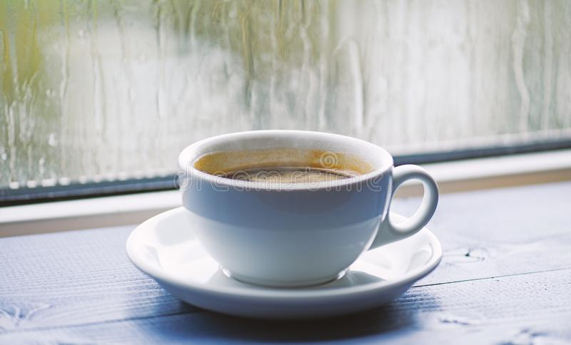 Wet glass window and cup of hot coffee. Autumn cloudy weather better with caffeine drink. Enjoying coffee on rainy day. Fresh brewed coffee in white cup or mug stock photography