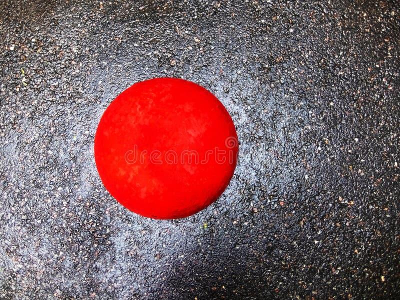 Wet gray asphalt, red concrete ball. stock photography