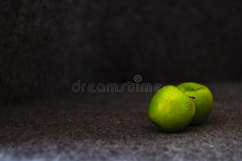 Wet green apples. Wet green Granny Smith apples on a gray background. Taken in a low key stock photos