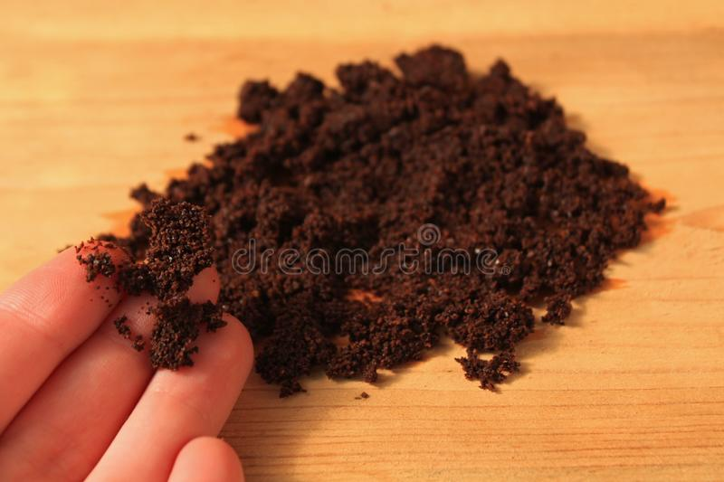 Wet ground coffee texture on wooden background. Wet ground coffee in hand on wooden background. Tablet of freshly prepared espresso. Coffee scrub for face and royalty free stock images
