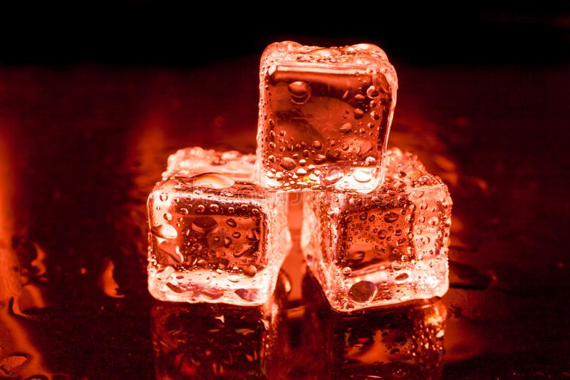 Wet ice cubes on black background with red light. Abstract, bar, beautiful, blocks, blue, bottles, bright, bubble, clean, clear, closeup, cold, cooler, crushed stock image