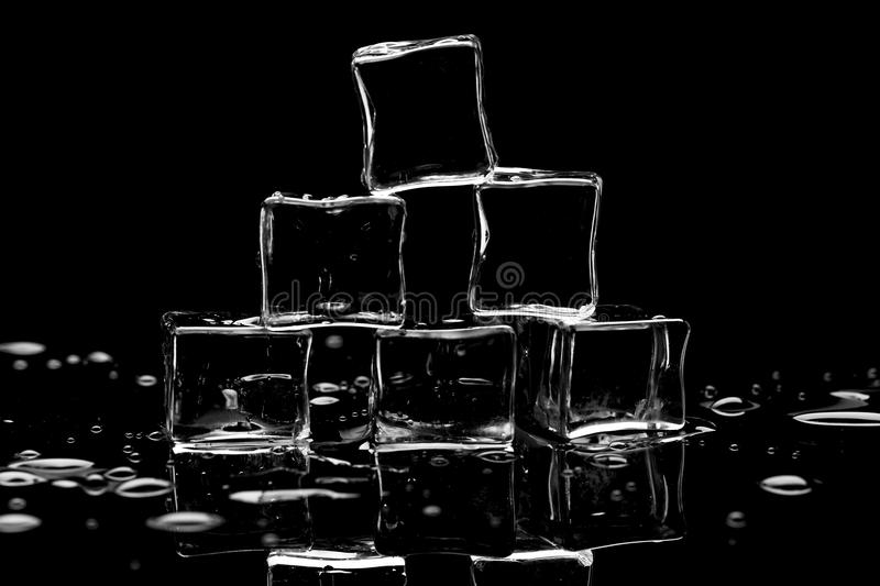 Wet ice cubes on black background with water drops and reflections royalty free stock images