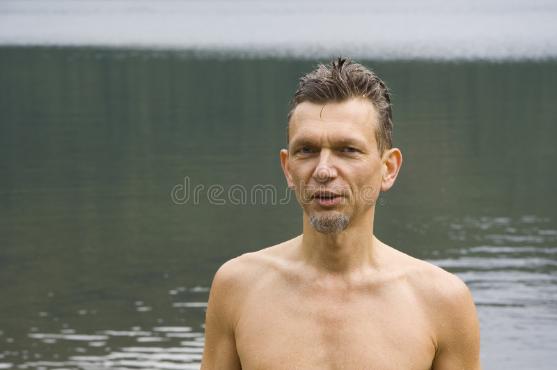 Wet man after a swim in a lake royalty free stock image