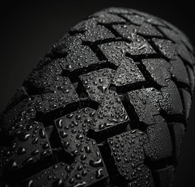 Wet motorcycle tire tread. Close-up shot of classical motorcycle tire tread in wet weather condition stock photos