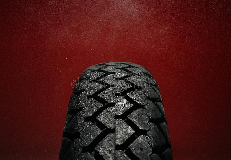 Wet motorcycle tire tread. Close-up shot of classical motorcycle tire tread in wet weather condition stock images
