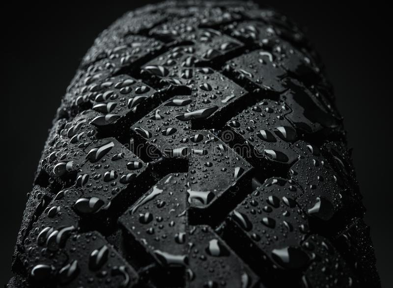 Wet motorcycle tire tread. Close-up shot of classical motorcycle tire tread in wet weather condition royalty free stock photos