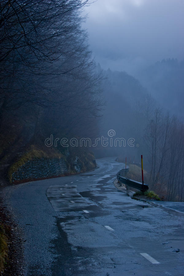 Wet mountain road at dusk royalty free stock photos