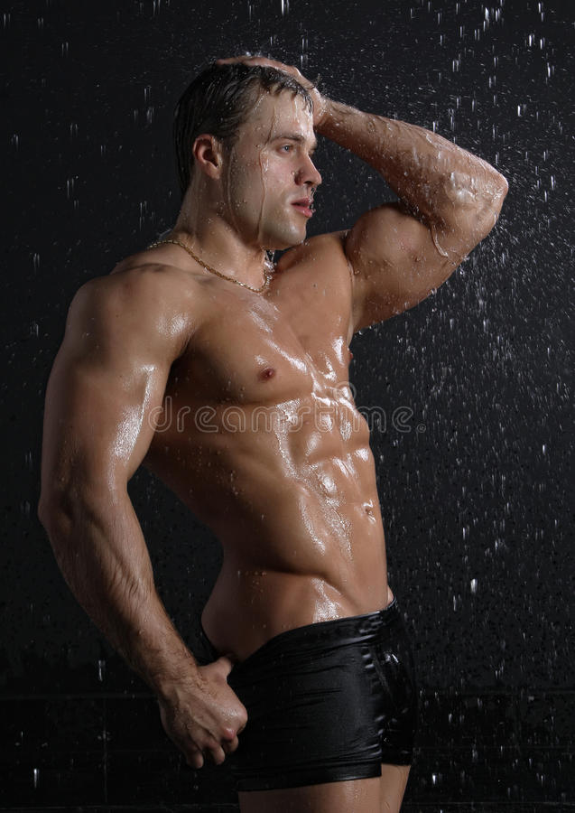 Wet Muscle Young Man Posing Under The Rain Stock Photo