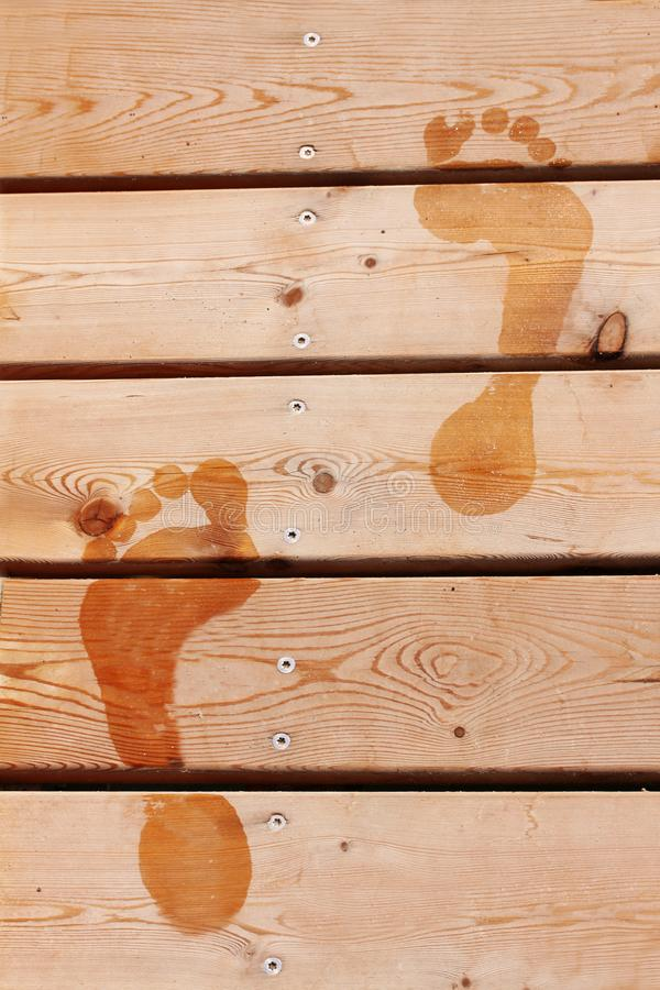 Wet prints of two human feet on brown wooden deck floor. Close up stock images