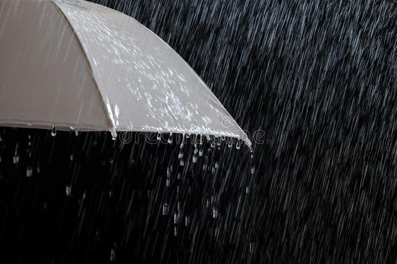 Wet protection umbrella in stormy weather with natural thunderstorm, on black background,. Wet protection umbrella in stormy weather with natural thunderstorm stock photo
