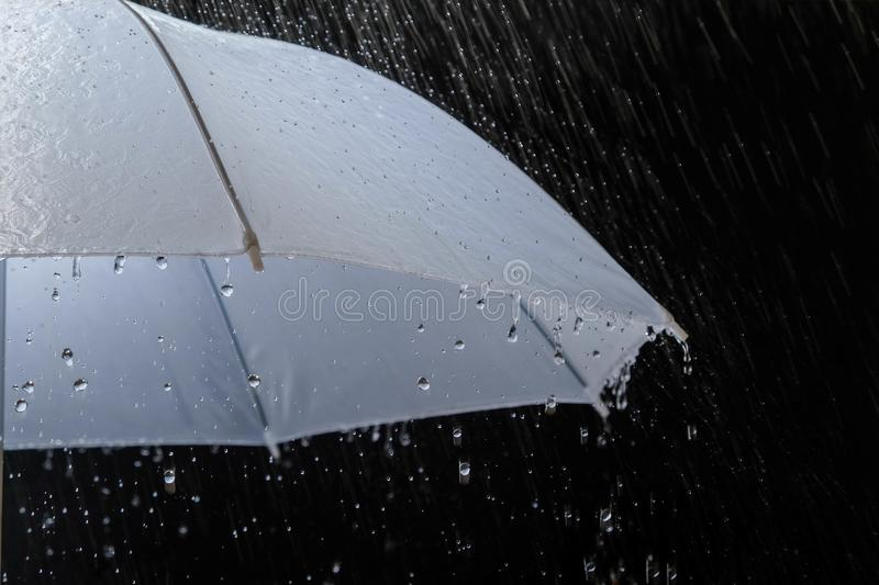 Wet protection umbrella in stormy weather with natural thunderstorm, on black background,. Wet protection umbrella in stormy weather with natural thunderstorm royalty free stock images