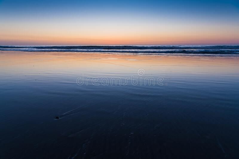 The wet, rippled sand of a beach reflects purple and yellow hues of sunset. The purple, pink, and yellow hues of sunset reflect in the wet, rippled sand of a stock photo
