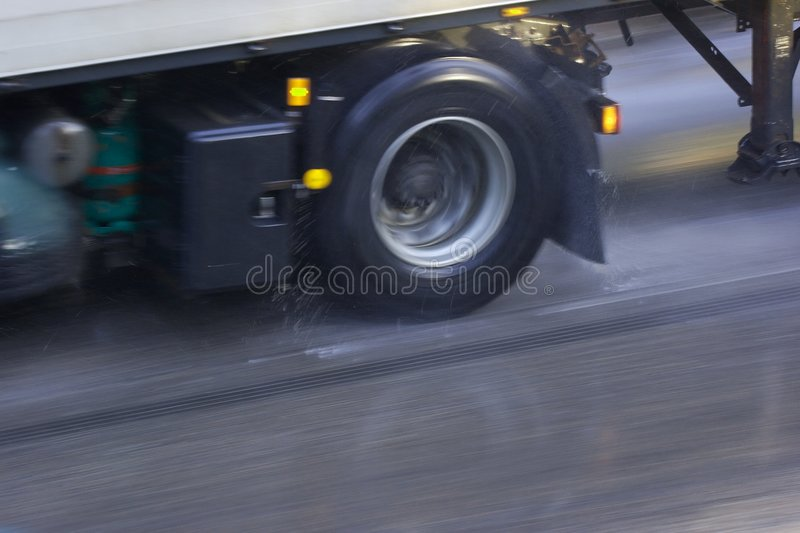 Wet Road. Wheel of a fast truck on wet road with motion blur royalty free stock image