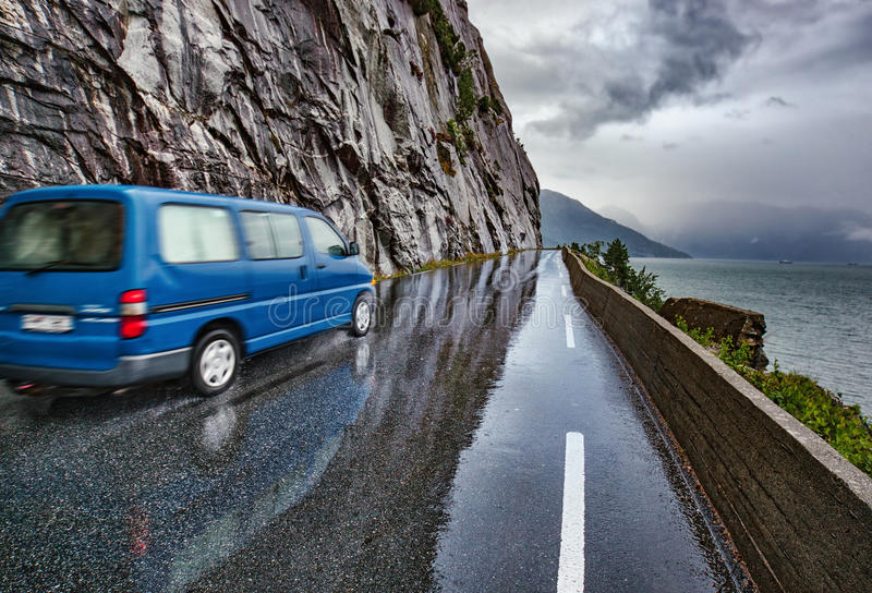 Wet road with car. Wet road after rain with blue car in Norway. Car driving safety concept royalty free stock photography