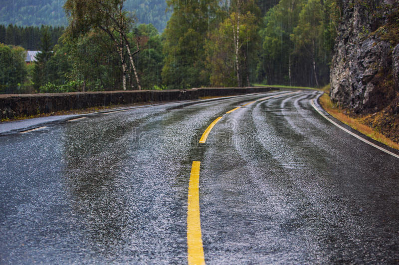 Wet road. With turns at rain in Norway. Car driving safety concept royalty free stock photography