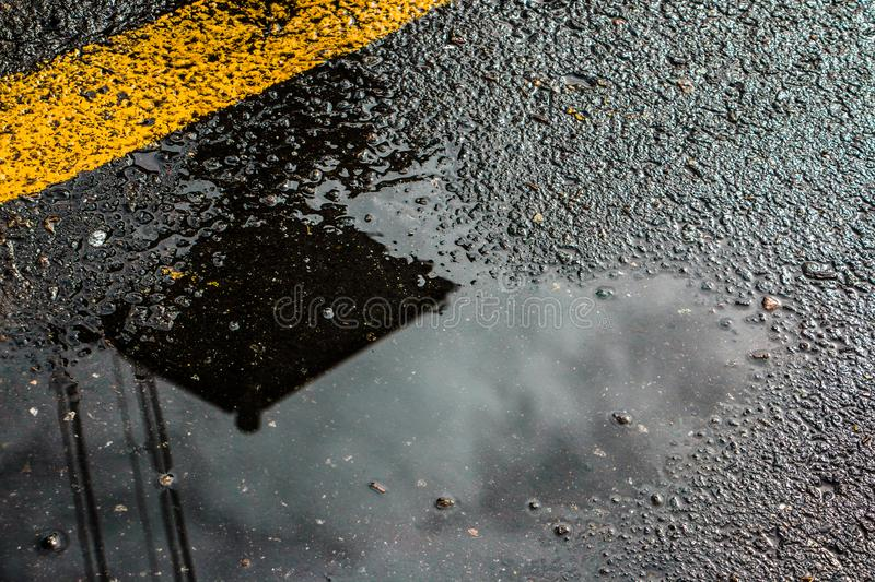 A wet road. With a yellow line and reflection royalty free stock image