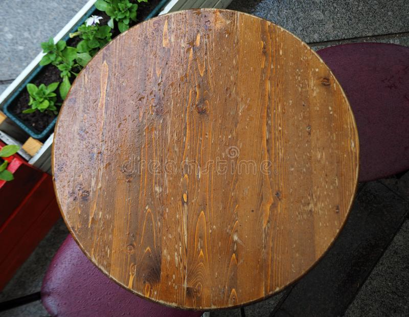 Wet round wooden table top view with drops of rain on it royalty free stock images