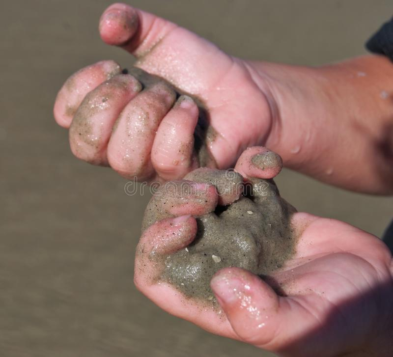 Wet sand childs hand. Wet sand in a childs hand royalty free stock image