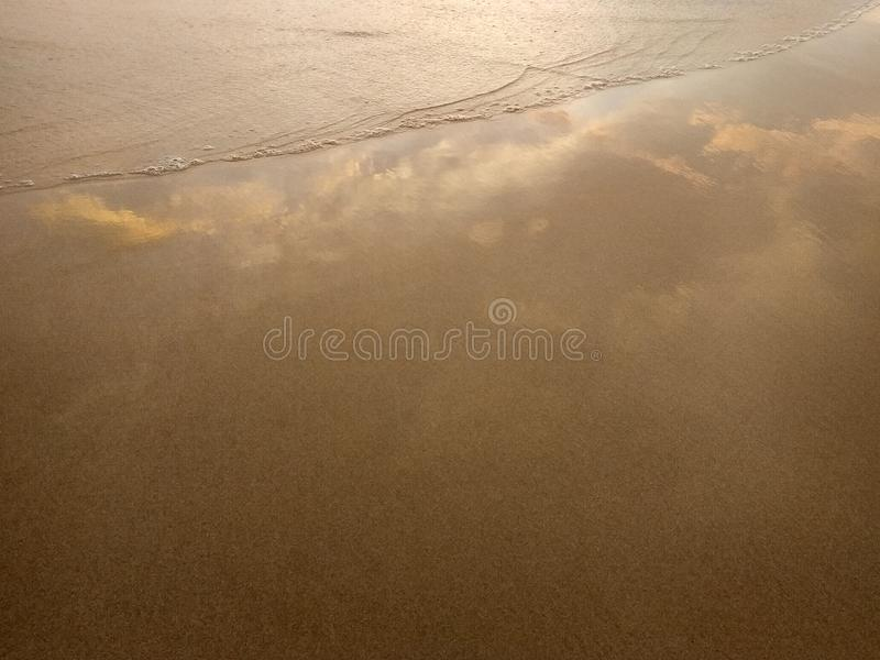 Wet sand with a raging wave, reflecting the sky with clouds in pastel colors royalty free stock photo