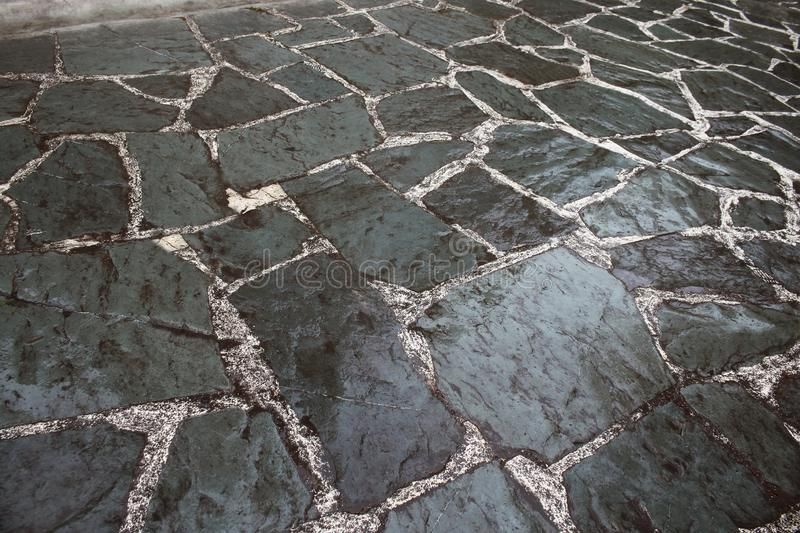 Wet shiny gray tiled mosaic pavement floor. With scratches, architecture, block, design, pattern, paving, road, rough, street, surface, texture, background stock photo