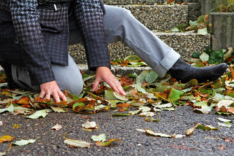 Wet and smooth streets can lead to accidents. A woman has slipped on wet foliage royalty free stock photos