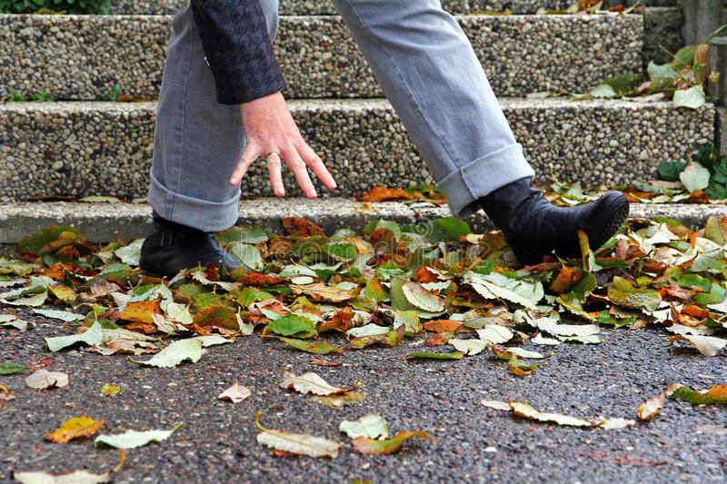 Wet and smooth streets can lead to accidents. A woman has slipped on wet foliage royalty free stock photo