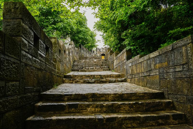 Wet stairway of stone wall in trees after rain,Guiyang,China. Wet stairway of stone wall with parapet and battlements in trees after the rain,Qingyan town royalty free stock image