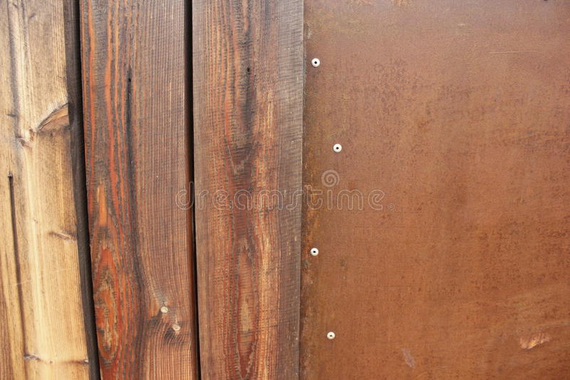 Wet wall of wooden planks pieces of rusty sheet of iron stock photography