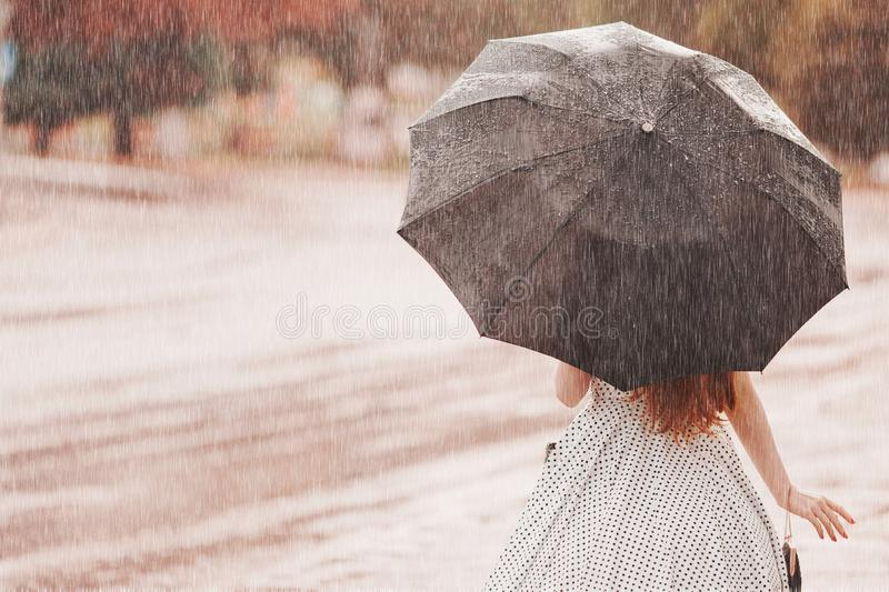 Wet weather. Autumn rain. Depressed girl in polka dots dress hold black umbrella. Raining in city. Wet umbrella against the backd royalty free stock image