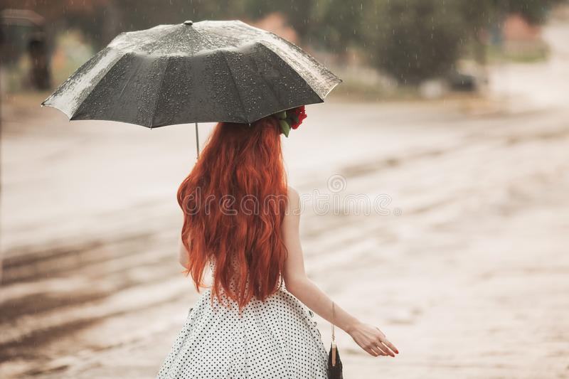 Wet weather. Autumn rain. Unhappy girl in polka dots dress hold black umbrella. Raining in city. Wet umbrella against the backdro. P of the street. Woman was royalty free stock image
