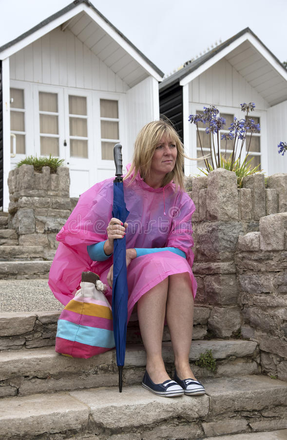 Wet weather and holidaymaker at seaside. Unhappy female holidaymaker wearing a poncho at a dismal wet seaside resort in the UK Sitting outside a beach hut royalty free stock photos