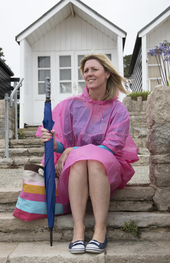 Wet weather and holidaymaker at seaside. Holidaymaker wearing a poncho at a dismal wet seaside resort in the UK Sitting outside a beach hut stock photo