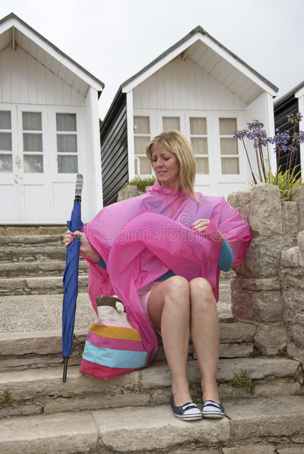 Wet weather and holidaymaker at seaside. Holidaymaker wearing a poncho at a dismal wet seaside resort in the UK Sitting outside a beach hut stock image