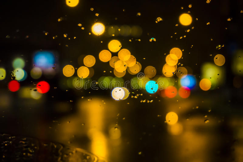 Wet the window with the background of the night city traffic view. royalty free stock photos