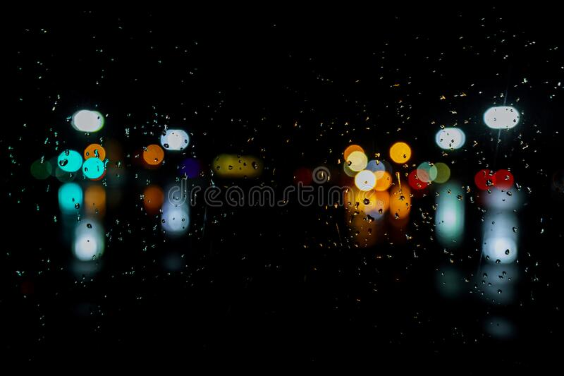 Wet the window with night rain and town lights background. Wet the window with night rain and town lights night city background royalty free stock photography