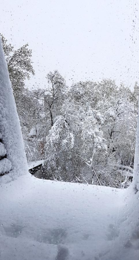 Wet window. Snow. View from the window. Snowy winter outside the window. Nice view from the window. Blizzard stock image