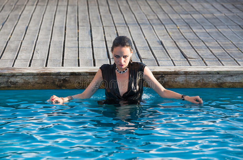 Wet woman in black dress in a swimming pool stock images