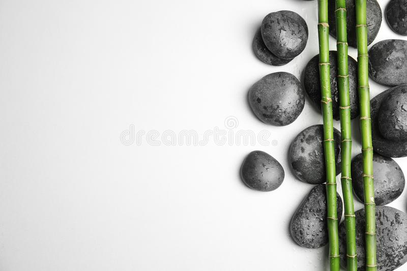 Wet zen stones and bamboo on white background, with space for text. Wet zen stones and bamboo on white background, top view with space for text royalty free stock photos