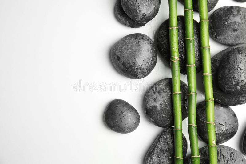 Wet zen stones and bamboo on white background, top view. With space for text royalty free stock photos
