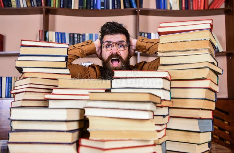 Wetenschappelijk ontdekkingsconcept Mens op geschokt gezicht tussen stapels van boeken in bibliotheek, boekenrekken op achtergron stock foto's