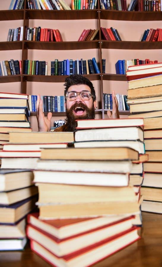 Wetenschappelijk ontdekkingsconcept Mens op opgewekt gezicht tussen stapels van boeken in bibliotheek, boekenrekken op achtergron royalty-vrije stock fotografie