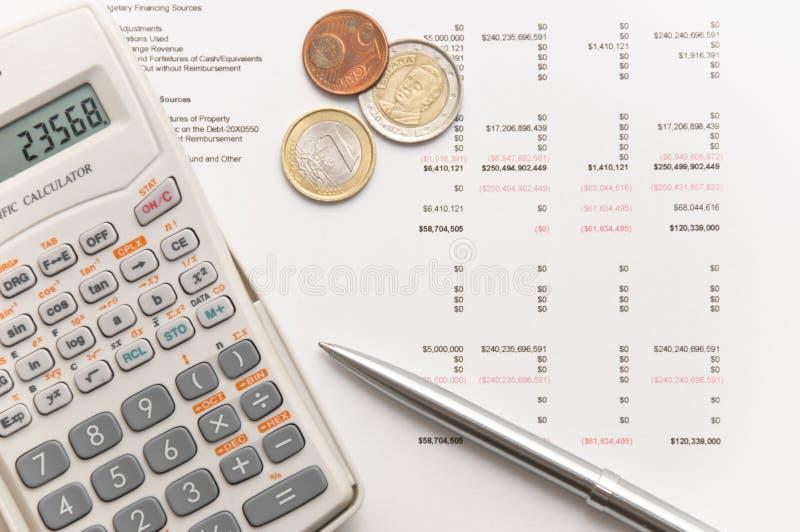 Wetenschappelijke calculator, muntstukken en zilveren pen royalty-vrije stock afbeelding