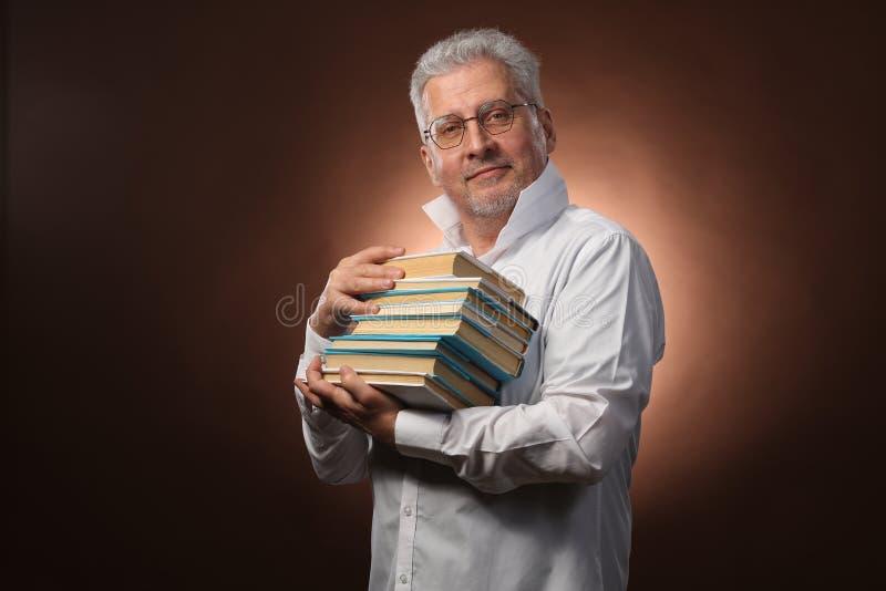 Wetenschappelijke denker, filosofie, bejaarde grijs-haired mens in een wit overhemd met boeken, met studiolicht royalty-vrije stock foto