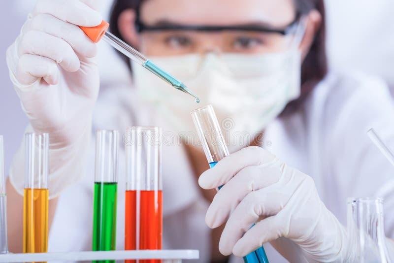 Wetenschappelijke onderzoeker die reageerbuis op laboratorium met behulp van Selectief F stock foto's