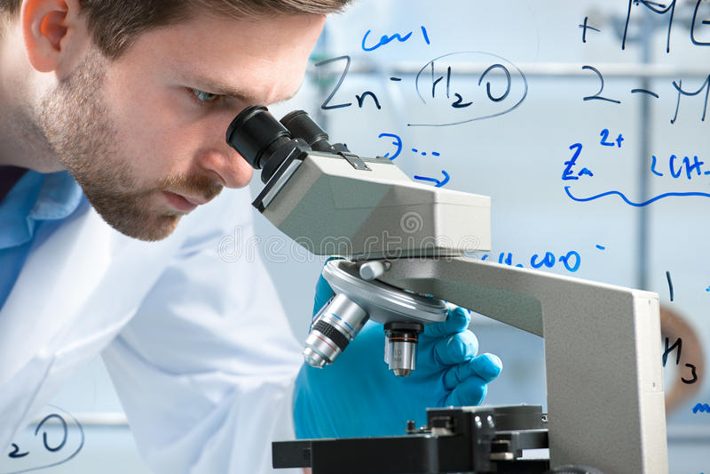 Wetenschapper die door een microscoop kijkt royalty-vrije stock fotografie