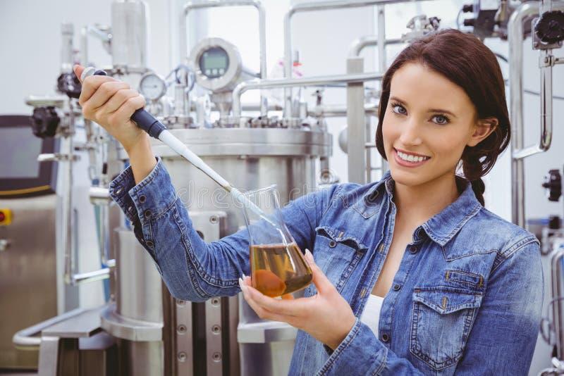 Wetenschapper die een experiment met een pipet en een beker voorbereiden stock foto