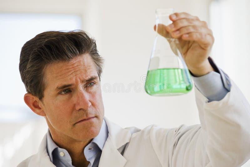 Wetenschapper die kruik van chemische producten steunt royalty-vrije stock afbeelding