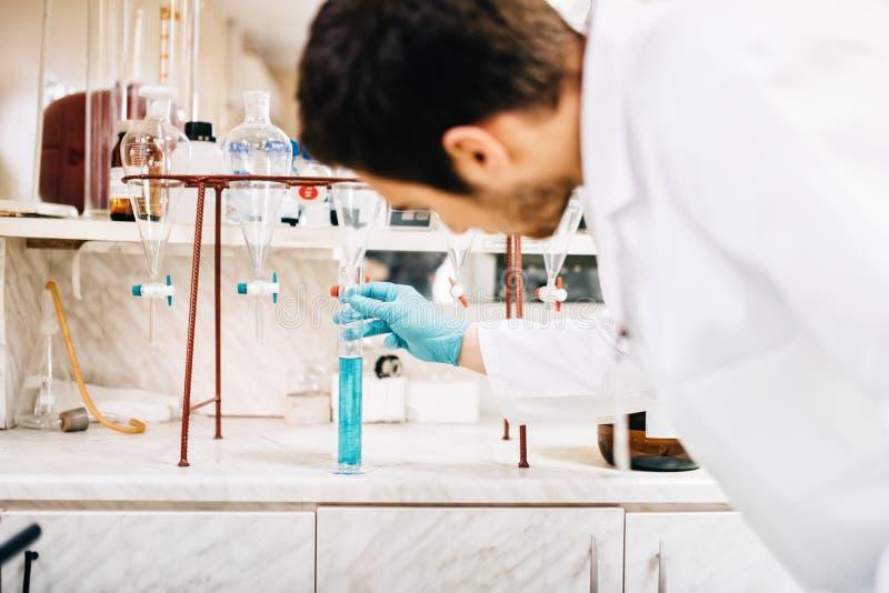 Wetenschapper die laboratoriumhulpmiddelen, reageerbuizen in kliniek, apotheek en medisch onderzoeklaboratorium met behulp van stock afbeelding