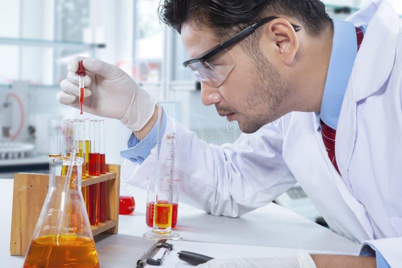 Wetenschapper die met chemische vloeistof werken stock foto